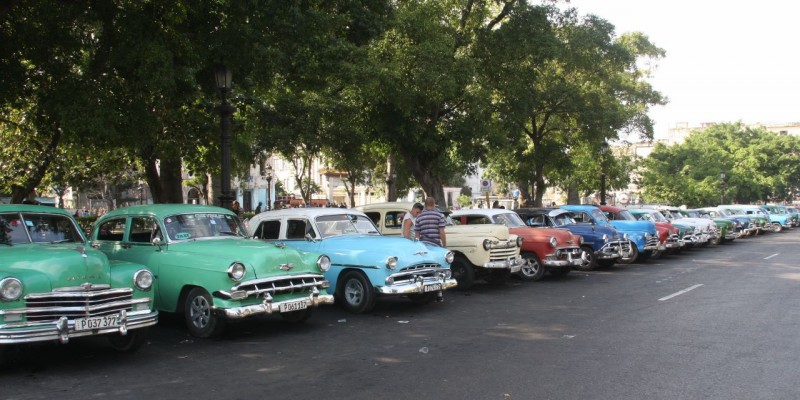 "This is not a Saturday gathering of an old car club.  These are all working taxi cabs waiting for fares in the Parque de la Fraternidad in downtown old Havana.  Hundreds of pre-1960 American cars still ply the streets and highways of Cuba.  I had heard about them for years and they were my main reason for visiting Cuba.  After the Revolution in 1959, all importation of American goods ceased.  As I understand it from asking around in my terrible Spanish, for years, no new vehicles from any country were allowed into Cuba, and only certain individuals who had cars prior to the Revolution were allowed to keep them.  Over time the government ""acquired"" most of them and leased them back the people.  Only in the last three years have individuals been allowed to own them outright.  The pride of ownership radiates from the owner's faces.  These cars provide a glimmer of joy in an otherwise bleak existence."