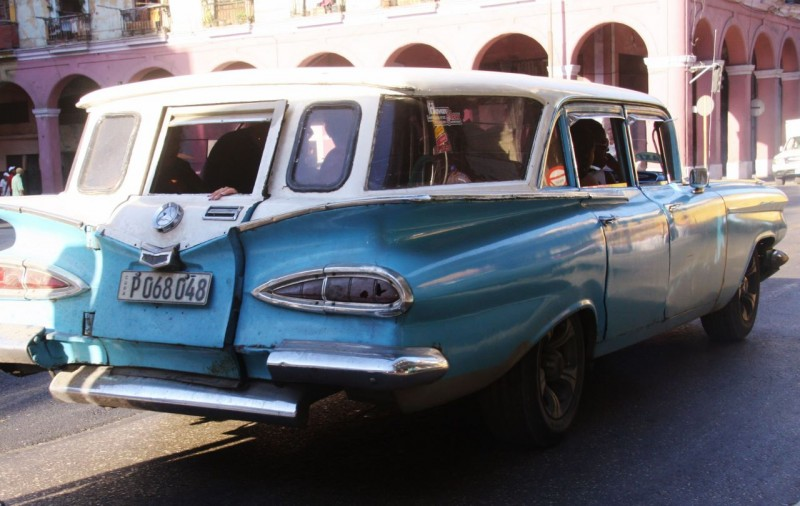 This 1959 Chevy wagon has been modified with an opening back door and is converted inside with side mounted seats facing inward. It is used as a bus.