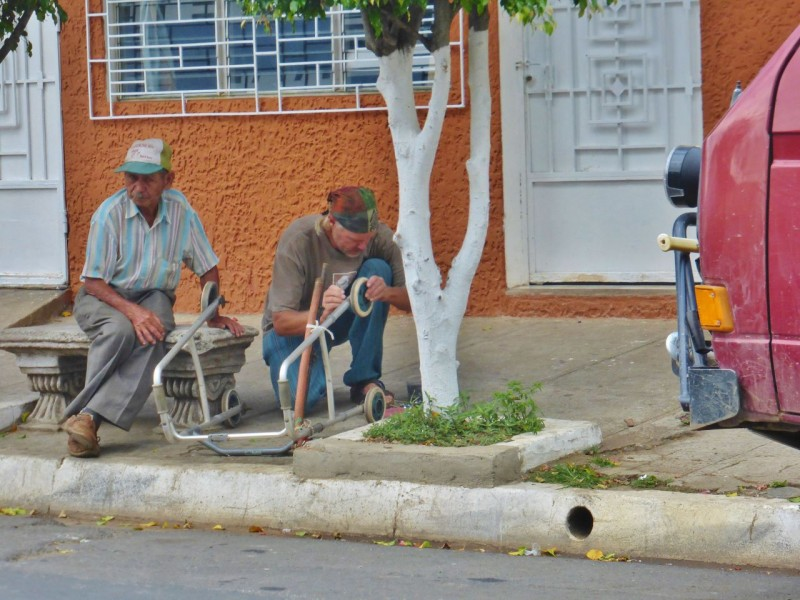 While we waited for our food, I spotted this poor old guy (yeah, the one on the left!) trying to get down the street with his walker, but its wheels kept falling off. I dug some new bolts and nuts out of Charlotte's stash and soon had the guy motoring down the road.