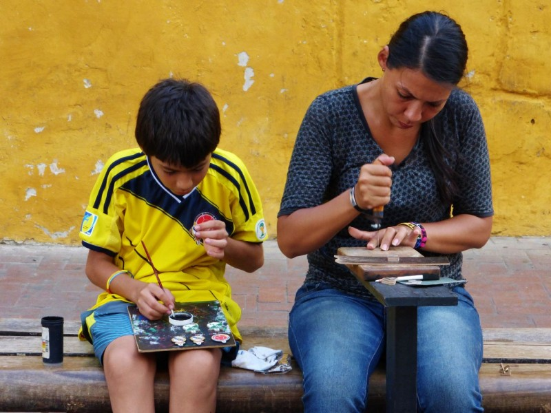 A resourceful mother and son team.  Mom was cutting little soccer ornaments out of wood, while the youngster painted them in bright colors.