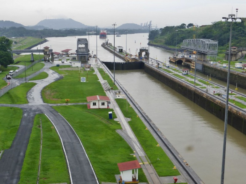 This is the infamous Panama Canal as seen from the observation tower at the Miraflores Locks.   These are the first of three sets of locks that a boat must pass through when traveling from the Pacific to the Caribbean.  We are looking southeast (weird huh?) here, back towards Panama City.  In the distance is a red and blue natural gas freighter approaching the locks.  There are two shipping lanes in each lock.  This boat is going into the far lane where the gates are open.  Notice how low the water level is in the far lock, matching the level in the near lock and the level in the canal itself.
