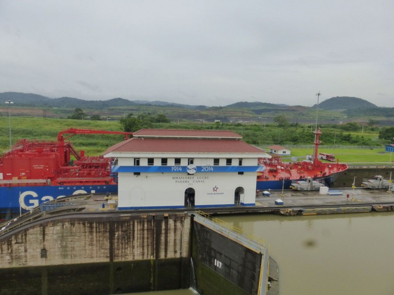 "Now the tugs have just about pulled the huge freighter completely into the next lock.  Note the old control house in the foreground which says Miraflores Locks 1914 – 2014.  The canal was originally begun by the French in 1881.  After many setbacks with financial, engineering and medical struggles due to malaria and yellow fever, the French went broke, gave up and the USA took over the project in 1904.  Incorporating advances in medicine and cleanliness for the thousands of immigrant workers, as well as mechanical advances in digging technology, we managed to finish the project.  The first boat passed through ""The Big Ditch"" in 1914.  Some trivia:  By the end of the project, 60 million pounds of dynamite had been used and enough holes were drilled through the solid rock of the country to reach completely through the earth and 900kms beyond! A huge expansion project is underway to create new, much larger sets of locks for much larger ships.  You can just see the digging going on in this photo at the left where the reddish strip is.  Today, container ships carrying up to 4500 containers can fit through the existing locks.  In the future, ships carrying 12,000 containers will be able to traverse the canal."