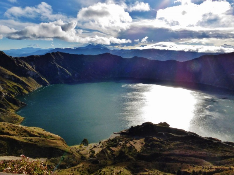 "From all accounts, Quilotoa, a crater Lake at around 12,000ft elevation was supposed to be fantastic and worth the out of the way drive.  We had even met a Swiss woman who said it was the most beautiful lake she had ever seen.  So off we went, continuing on our Volcanoes tour.  First south to the town of Latacunga to stock up on groceries for all of that camping and hiking we were looking forward to. Unfortunately, it was dark before we reached the lake, so we had to find a hiding place to camp off of the main road.  It was difficult, and we were both crabby by the time we wheeled our way up a steep farm track and onto a presumably deserted soccer field.  Sleep was just about upon us when we were visited by a pack of broomstick and hoe wielding villagers.  We couldn't understand a word of their local dialect, and it felt like we were in a bad medieval movie.  I chickened out, staying in the back, while Ned addressed them, playing the ""No comprendo"" role yet again.  They eventually trundled away harmlessly.  An hour later, having just fallen asleep, we were visited by the police, sirens blaring and lights flashing.  Evidently the medieval villagers have cell phones.  The cops were actually very polite and apologetic.  The village was worried that we were the robbers!  We were left in peace the rest of the night, but pent up adrenaline kept us awake.  Ditching our camp spot at 7am, we had visions of a nice breakfast and coffee at the lake.  What we found instead was that the town was a dump.  No eggs, no coffee, no restaurants at all.   We went to the lookout to see this wondrous crater lake, but the freezing wind was so strong I had to hold on to the railing to keep from being blown away.  The lake was pretty cool, but the whole vibe of the place was down-trodden and inhospitable.  We shot this poor photo taken directly into the rising sun and abandoned the plot."