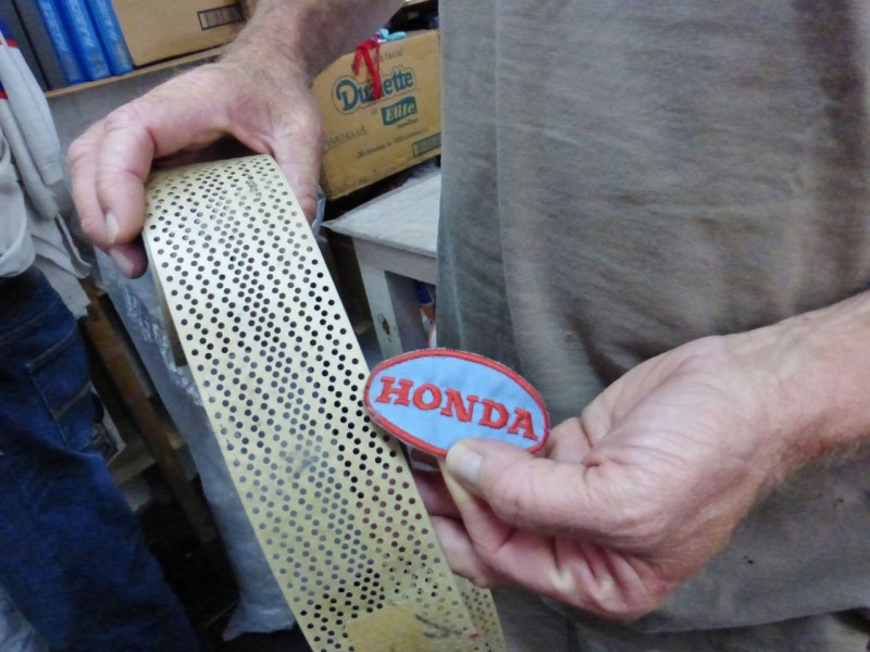 But less than fifteen years ago, embroidery was created by a mechanical machine that read a ticker-tape like strip.  The code on this strip produced this little Honda patch.  Hans showed us shelves full of hundreds of these now obsolete tapes.  It their day, each tape cost the company US$6,000 each and was only good for one style of patch.