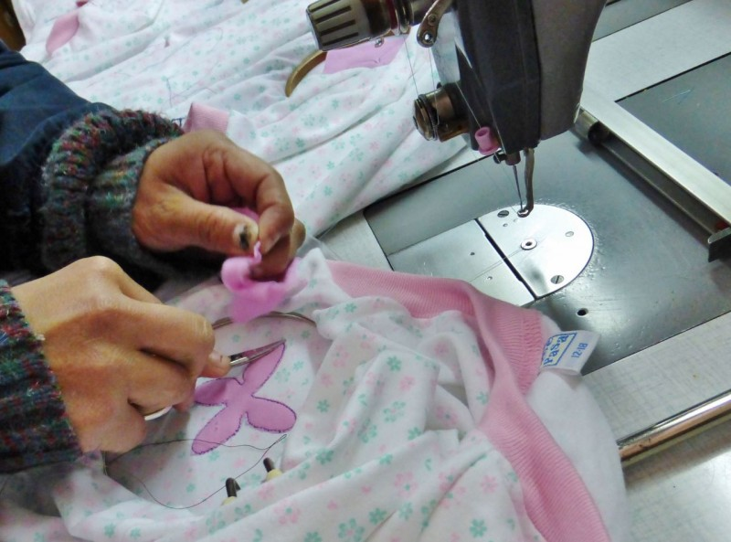 The hand work going on was amazing.  After the pink star-like thingy was sewn onto the garment by a machine, a lady hand cut away the excess material with manicure succors, one after the other, all day.