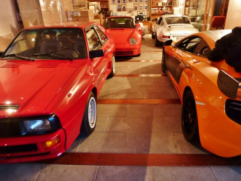 "Ned will share this one, of course:  Sebastian had been telling me about this friend of his that had some ""amazing"" cars.  As I was interested in seeing them, he arranged a visit. We only saw part of the collection which is scattered at various properties around town.  These beauties were housed in the basement of a beautiful home in the foothills of Santiago. Amazing does not begin to describe the caliber of these vehicles.  Seen here left to right are an Audi Quatro Works Rally Car converted to street use, a Porsche 959, a Porsche RSR and a brand new, just-arrived-that-week McLaren 650S Sprint, the first and only one in South America. Rarified stuff indeed in any country!  Behind me is a Porsche Carrera GT and another, one year old McLaren.  These cars' owner also races in the Dakar in a Works Mini.  We plan to catch the Dakar race next month in northern Chile when we meet back up with Sebastian and family in Copiapó."