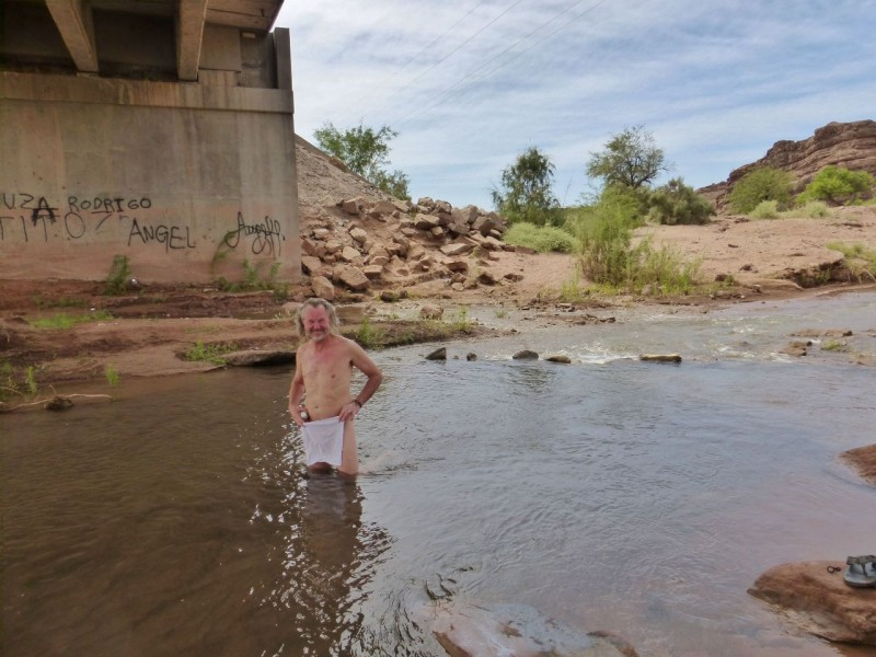 "While we had enjoyed our last three nights of camping out in the desert, we were not enjoying our sweaty selves.  We felt about as encrusted as the skid plate. Then, miraculously, about 10 minutes out of camp we spotted a rare desert river with clear water.  We quickly took advantage of this hidey hole under the overpass for heavenly baths in the Rio Huaco. Ned and I have a long history of being ""Trolls Under the Bridge,"" so this was a particularly fun stop."