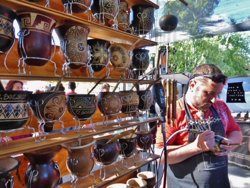 "Unlike many ""Artisan"" fairs, where it seems most of the wares are mass produced, the artists here displayed beautiful, hand crafted art.  This man was carving lovely designs on gourds for drinking mate (pronounced ma-tay).  Mate, short for Yerba Mate, is an herb which is packed in a mate vessel (of choice), covered with hot water and drunk through a straw-like contraption (called a bombilla).  Argentineans love their mates and are often seen ambling down the road, sipping on their mates with hot water thermoses (for refills) slung over a shoulder."