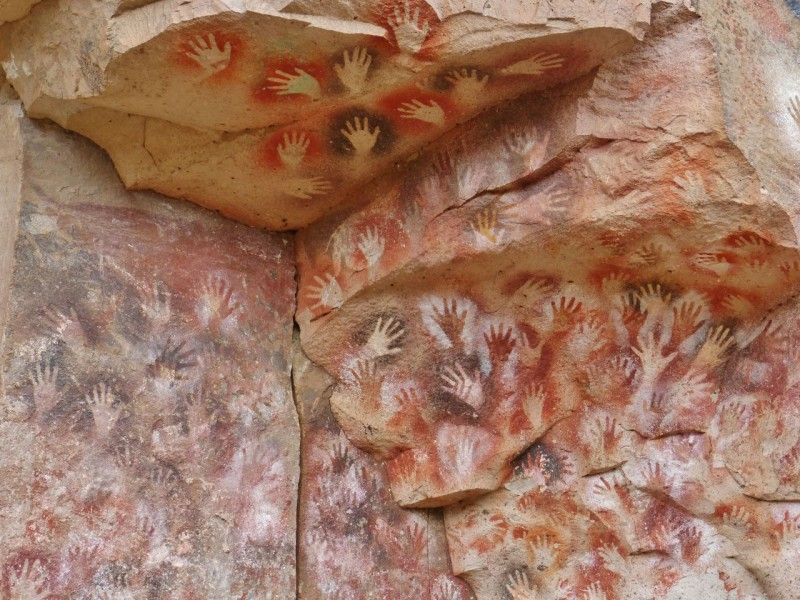 "There were thousands of hands ""stenciled"" on the long wall, preserved by an overhanging cliff.  The astonishing thing is that they were done 9,300 years ago in a two color process.  One color (paint made from local minerals, flora and spit) was put down as a base.  The second was sprayed by mouth through a straw over the artist's own hand."